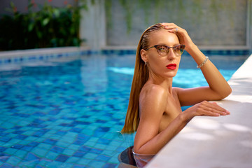 Enjoying suntan. Pretty young woman posing in swimming pool.