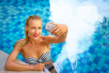 Vacation and technology. Pretty young woman using smartphone taking selfie in swimming pool.