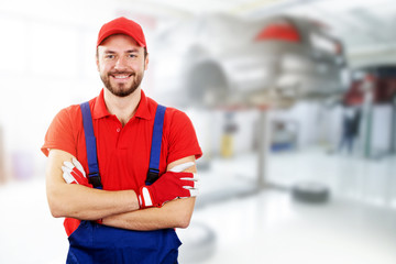 happy auto mechanic standing in car service garage