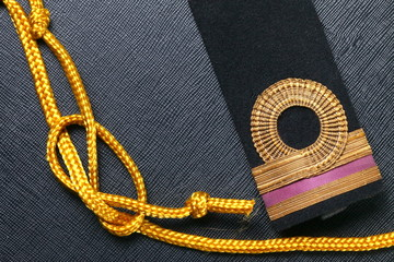 Vintage and old Royal Thai Navy arm put beside gold color rope represent Thai navy arm accessory to use with uniform.