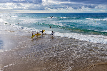 Spain, Canary Islands, Fuerteventura, La Pared. Group of boys goes surfing.