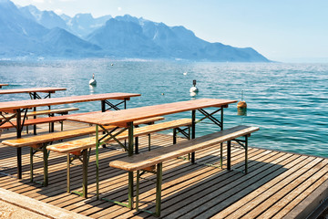Wooden tables with chairs for relaxation at Geneva Lake Montreux