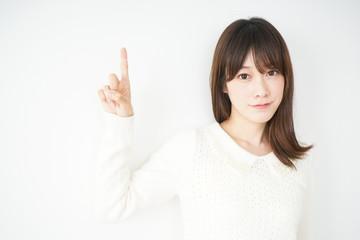 笑顔で指をさす日本人の若い女性