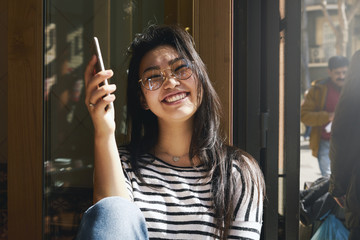 A portrait of a beautiful asian girl wearing glasses and smiling at the camera while sitting with a mobile phone in a modern coffee shop. Young blogger is having rest at the sunny day.