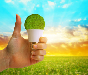 Hand with thumb up holding a eco LED bulb at sunset. Energy saving lamp.