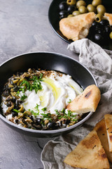 labneh middle eastern lebanese cream cheese dip with olive oil, salt, herbs, olives tapenade served in black bowl with traditional pita bread over gray texture metal background.
