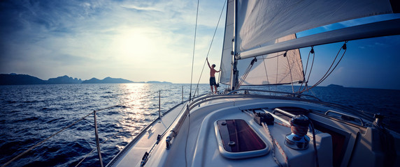 Young man standing on the yacht in the sea at sunset Fotomurais