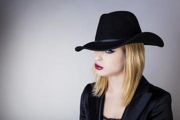 Portrait  d'une jeune femme avec un chapeau noir, le regard au loin