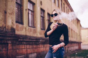 Blond woman in round sunglasses Vaping outdoors. Vapor concept.