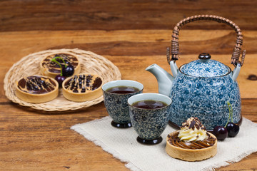 tartlets, basket cakes, sweet, tea on the wodden table