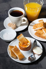 soft boiled egg, toasts, cup of coffeeand orange juice for breakfast on dark background, vertical