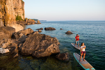 Attractive Young couple Stand Up Paddle Boarding