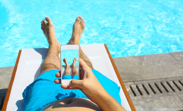 Young man lying on sunbed near pool with phone. Summer vacation and travel concept