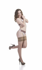 Sexy girl in underwear and stockings. Smiling posing. Studio shot on white background.