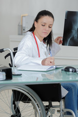 brave disabled female doctor examining x ray