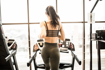 Young woman running on treadmill in gym