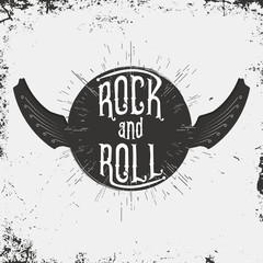 Rock and Roll music print. Grunge print for T-shirt with lettering and wings in guitar form. Monochrome vintage label, stamp with starburst and ray. Vector illustration