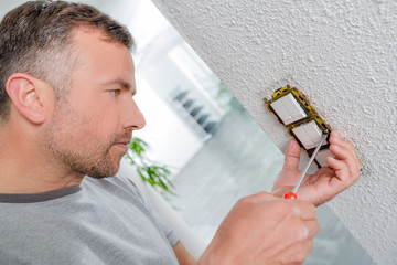 Man fitting light switches