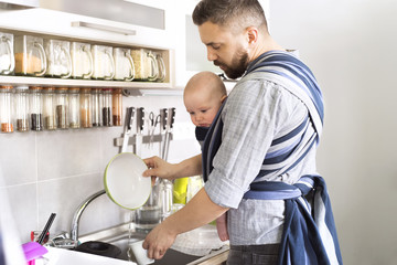 Father with baby son in sling at home doing the dishes