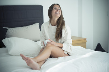 Happy young woman sitting on bed with cup of coffee
