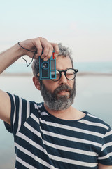 Portrait of bearded man taking photo of viewer with vintage camera