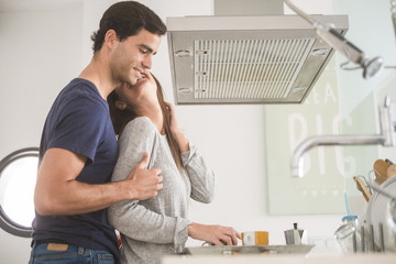 Happy young couple in love with coffee cups in kitchen