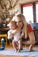 Smiling mother with baby and fitness equipment at home