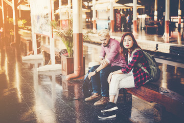 Hipster couple sitting on bench at the train station. Two young tourist are waiting to get on the train and begin their journey. Travel concept.