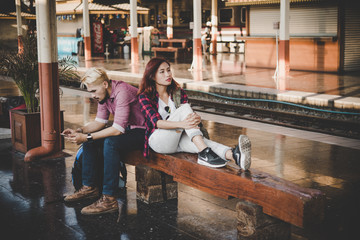 Young tourist couple with backpack sitting on bench at the train station. Two young tourist are waiting to get on the train and begin their journey. Travel concept.