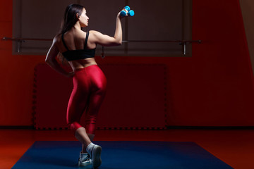 Young muscular woman bodybuilder with dumbbell in hand demonstrating body in gym, view from the back