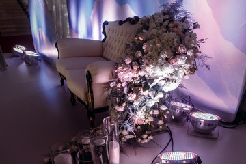 luxury wedding decor for photo booth of stylish chair sofa with amazing flowers in light and candles. expensive arrangements of decorations at wedding reception. space for text