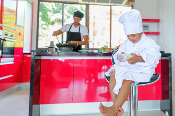 Cute little Thai boy in chef's hat and tunic sitting on a high chair in a modern style home kitchen. Dad is behind him making Thai food