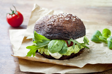 Grilled portobello bun mushroom burger. Vegan, gluten free, grain free, healthy veggies hamburger with guacamole, fresh vegetables and cashew cheese sauce.
