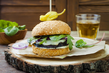 Grilled portobello mushroom burger. Healthy veggies hamburger with onions, arugula, cheese, spicy pickled hot peppers and tartar sauce. Copy space background