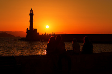 Silhouette of a couple making selfie on the beach at sunset in the city of Chania, island of Crete, Greece