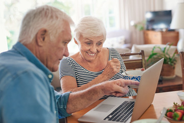 Smiling seniors using a laptop together over breakfast at home