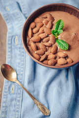 Organic chocolate smoothie, decorated with almonds and mint leaf on a blue denim background. toned picture. close up and selective focus