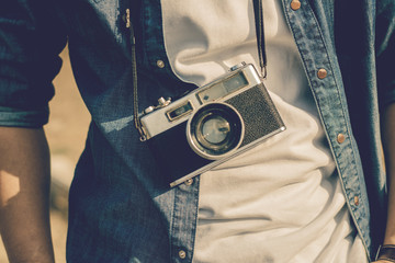 Young man tourist  standing and taking photos with vintage camera.