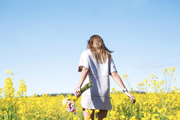 Woman in canola field, holding flowers