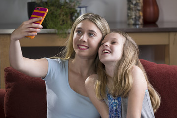 Two sisters using a cell phone to take their picture