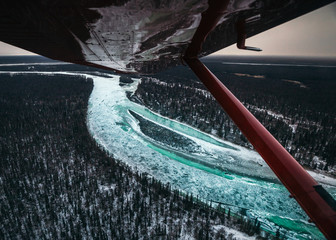 Frozen river and woodland reflected on air craft wing, Alaska, United States of America