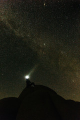 Man sitting on mountain against starry sky at night