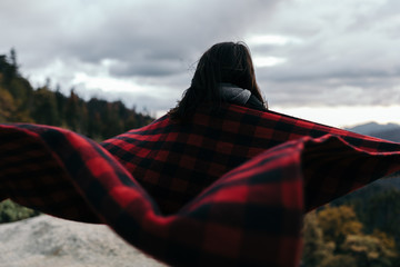 Person covered in blanket looking at view of mountains, woodland and stormy sky
