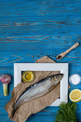 Fish in frame and various spices on blue wooden table.