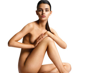 Ideal woman`s naked body. Photo of slim tanned woman sitting on white background. Health and beauty concept