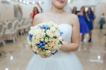 The bride in the cafe throws the wedding bouquet to one of her friends
