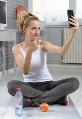 fitness woman taking photo with her smartphone,  after exercising