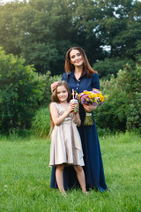 Mom and daughter are walking in a meadow, picking flowers and drinking juice