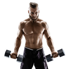 Guy with athletic body doing the exercises with dumbbells on white background. Photo of strong male with naked torso. Strength and motivation.