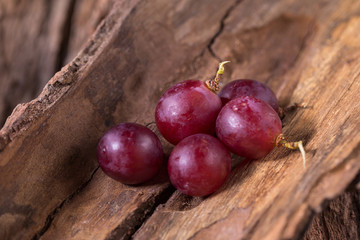 Bunches of fresh ripe red grapes on a wooden textural background